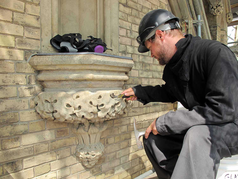 Homme nettoyant une sculpture de pierre