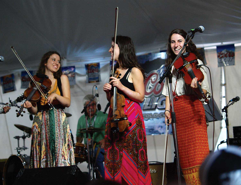 Trois femmes sur scène tenant des violons