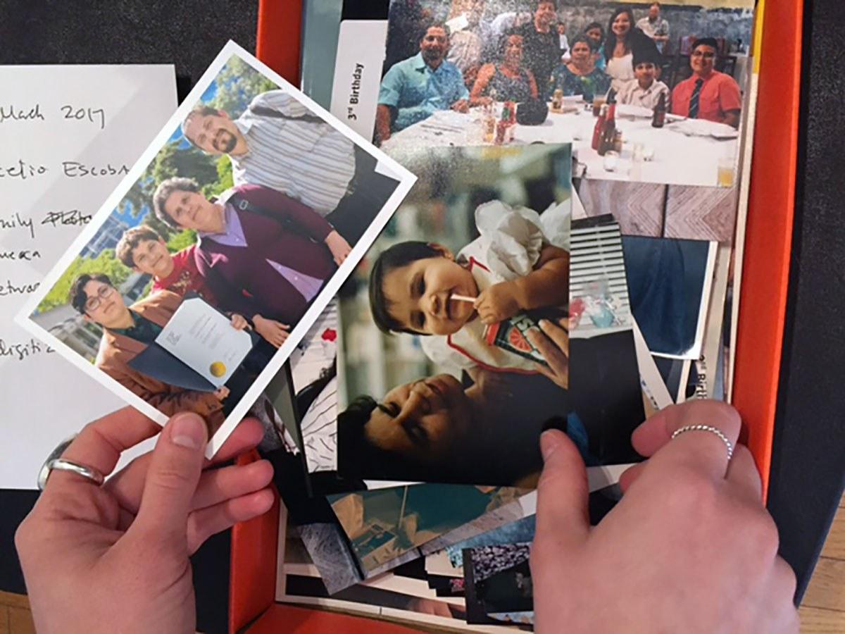 Paire de mains tenant des photos de famille