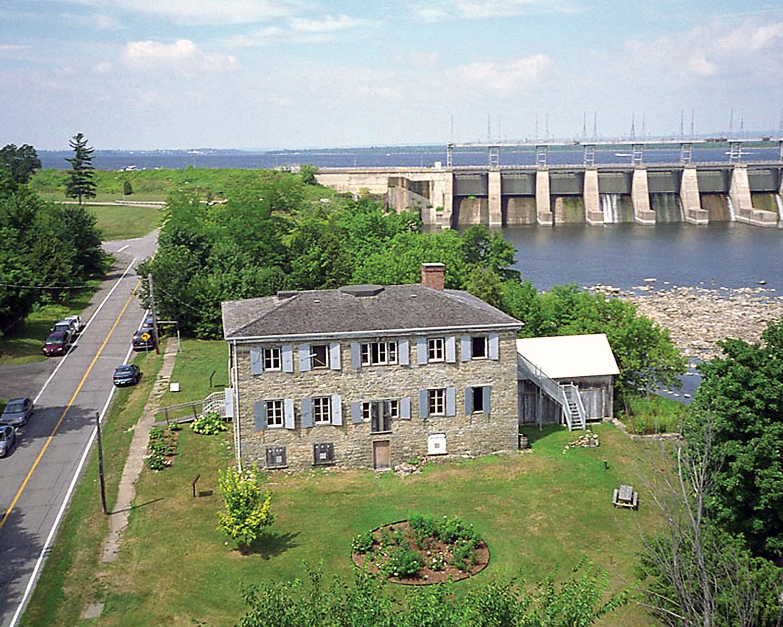 Photographie aérienne de la maison Macdonell-Williamson avec le barrage de Carillon à l'arrière-plan (Photo : Carl Bigras)