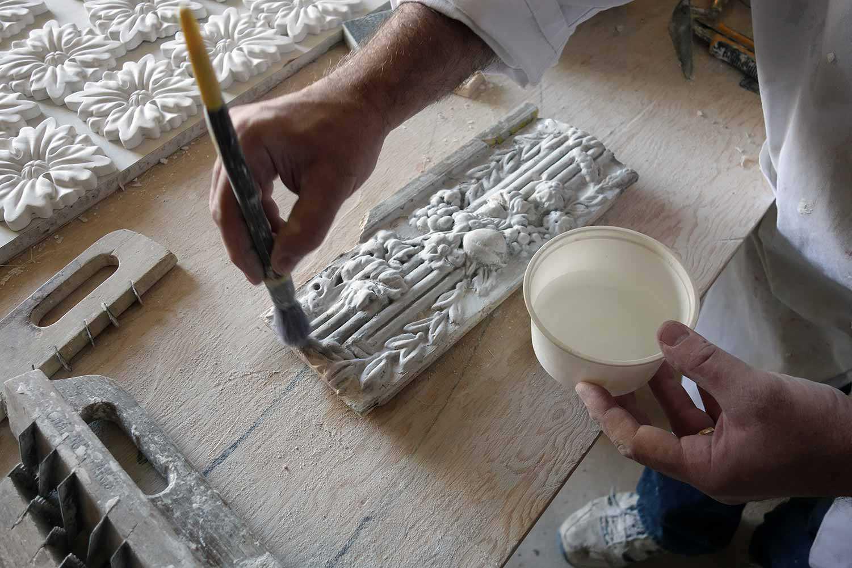 Travail de saturation de la peinture à la calcimine sur une moulure en plâtre décorative datant de 1817. En haut, à gauche, reproduction de rosaces. En bas, à gauche, outils de plâtrier traditionnels et artisanaux (MacdonellWilliamson House, Chute-a-Blondeau)