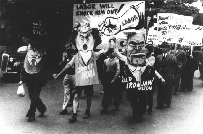 Photo en noir et blanc de travailleurs en costume et tenant des pancartes lors du défilé de la fête du Travail